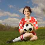girl soccer player holding ball