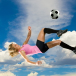 girl kicking ball in air
